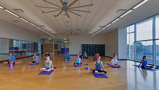 Group practicing yoga inside of a parks & recreation room