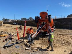 Pouring concrete to keep auger cast pile in place